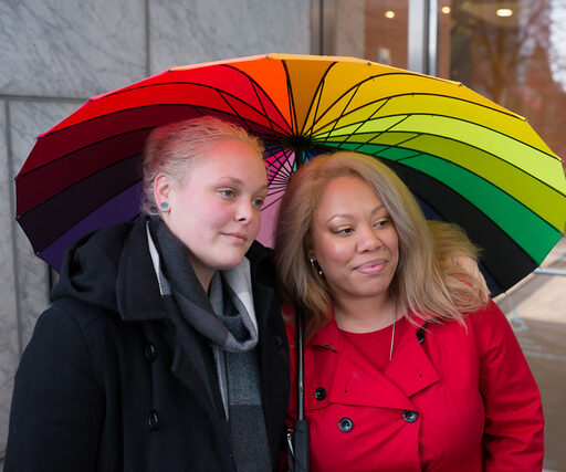 Mixed race queer couple standing together under a colorful umbrella